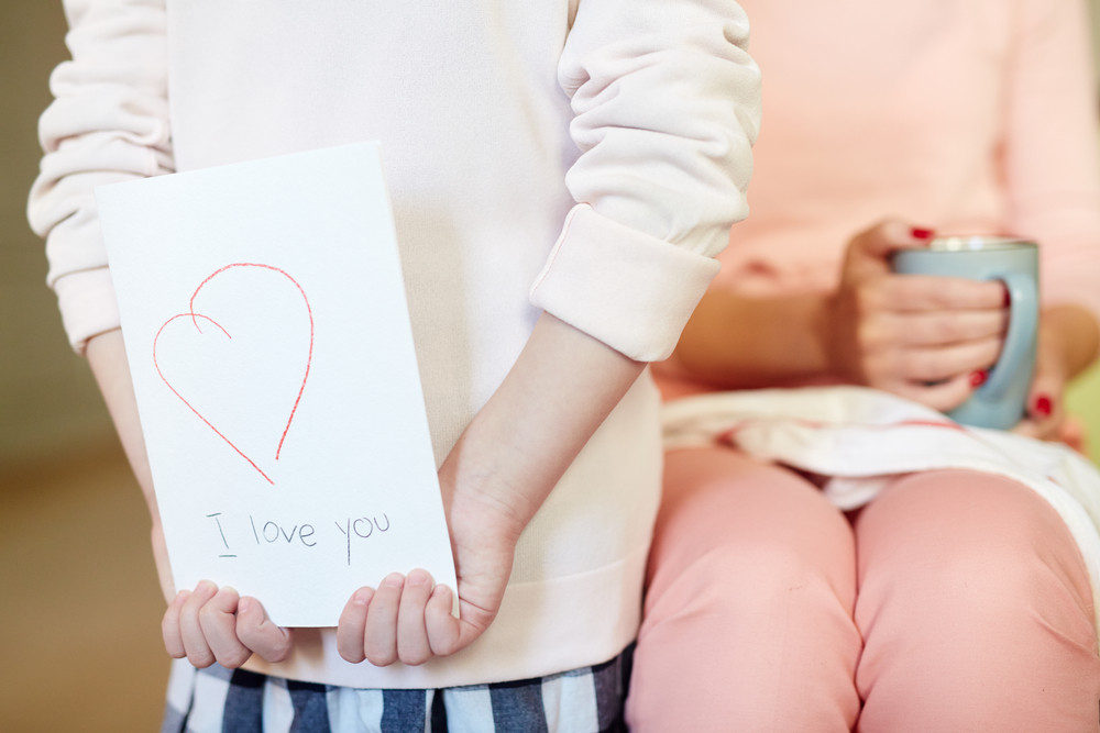Girl holding self-made card for her mother behind back