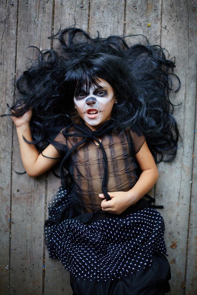Girl in black wig and halloween attire lying on wooden floor
