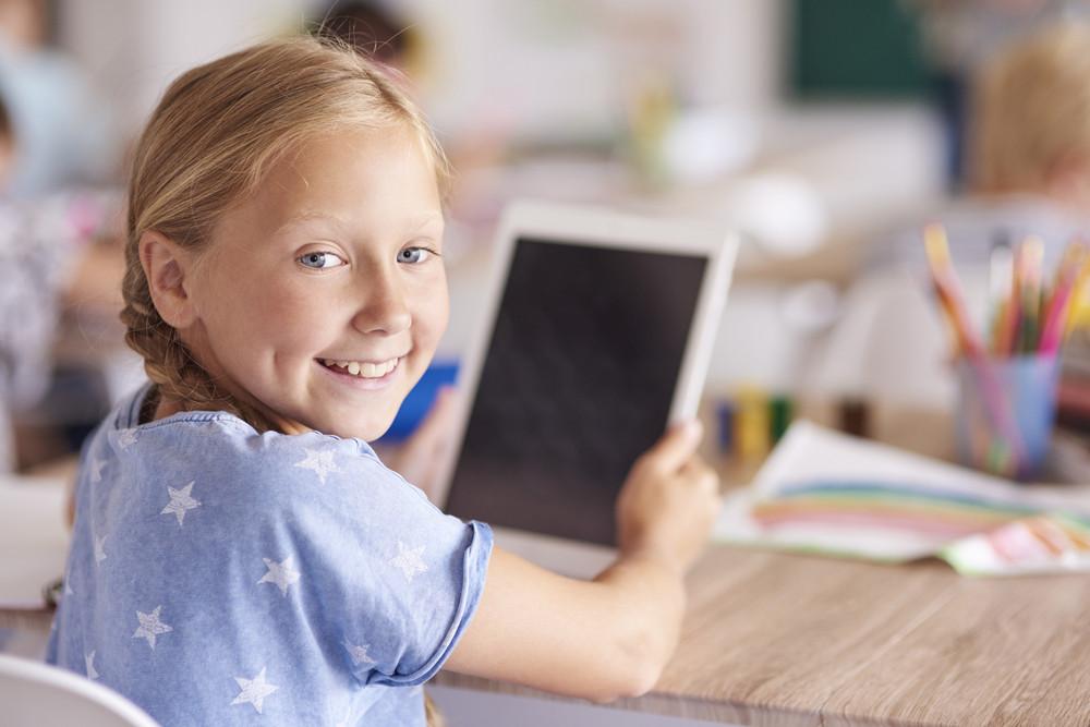 Girl using digital tablet at school
