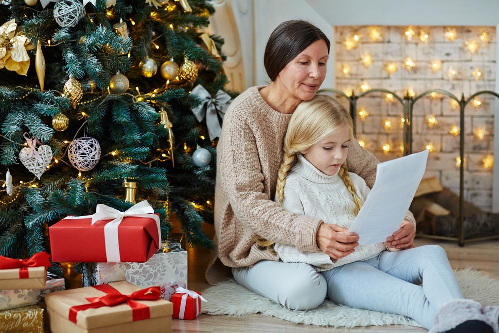 granny and grandchild reading letetr with xmas regards royalty free
