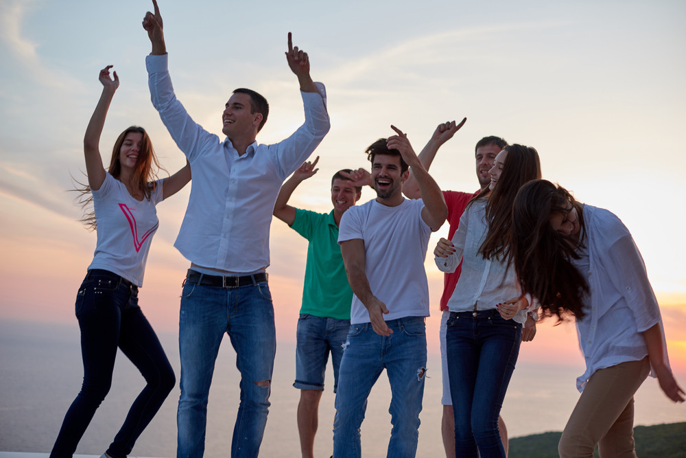 group of happy young people dancing and have fun on party in modern home bacony with sunset and ocean in background