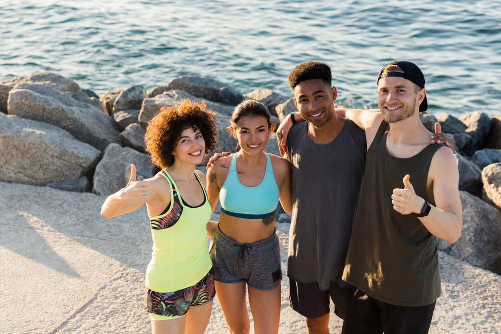 Group pf happy smiling friends in sportswear standing and showing thumbs up gesture outdoors