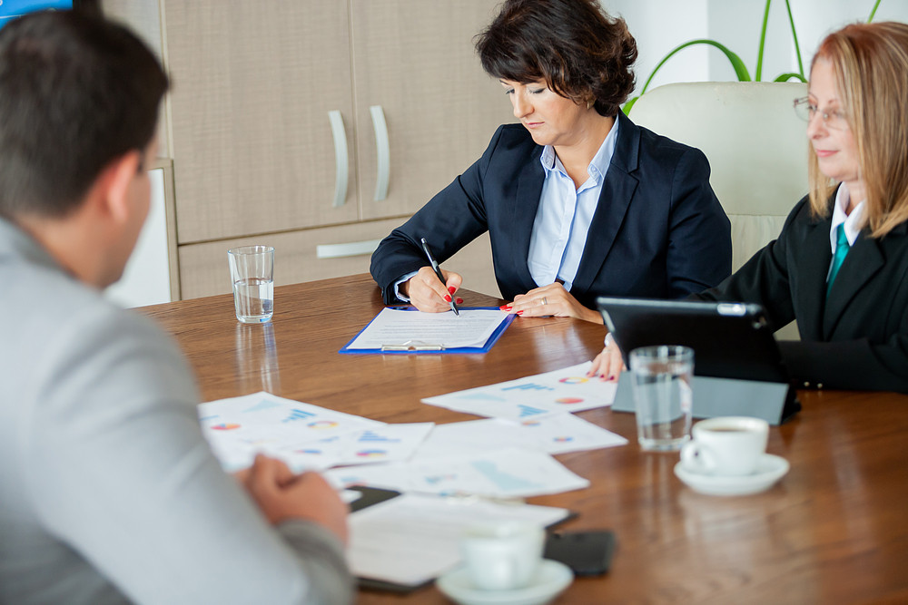 Hand of businesswoman signing a contract in the meeting room. Close up image