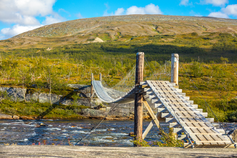 hanging rope wooden bridge over the mountain river
