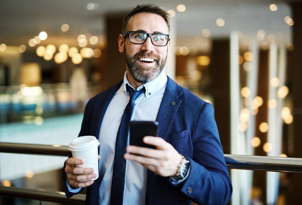 Happy businessman holding glass with coffee and cellphone