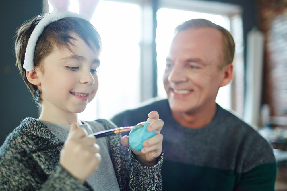 Happy child painting egg in blue color