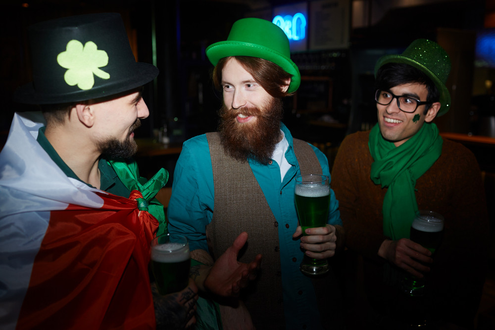 Happy friends talking and having beer on St Patrick day
