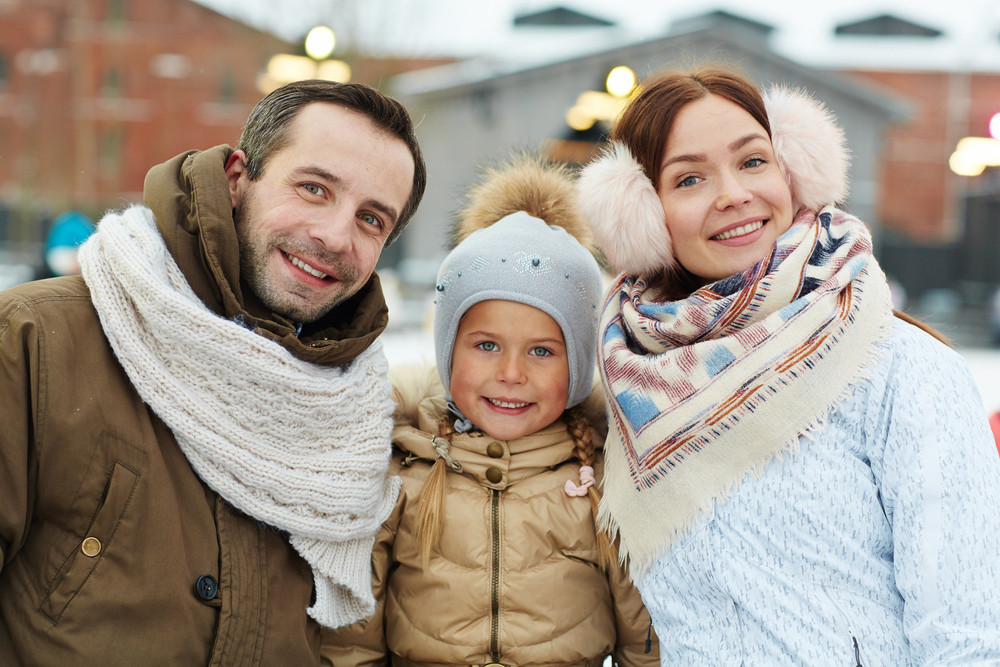Happy girl and her parents in winterwear looking at camera