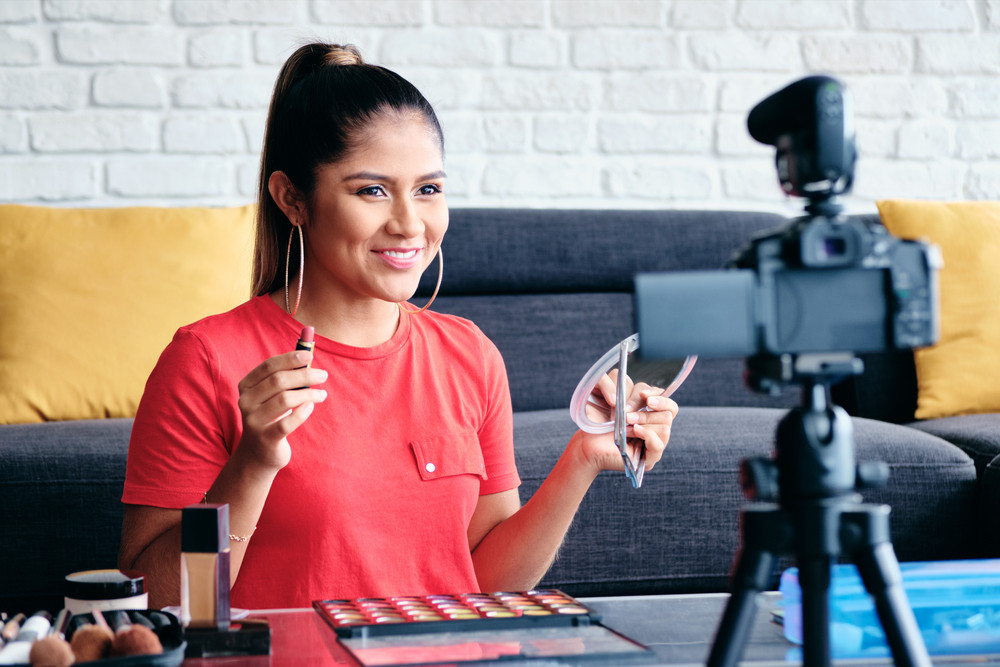 Happy girl at home speaking about make up in front of camera. Video blogger recording message for social media and internet