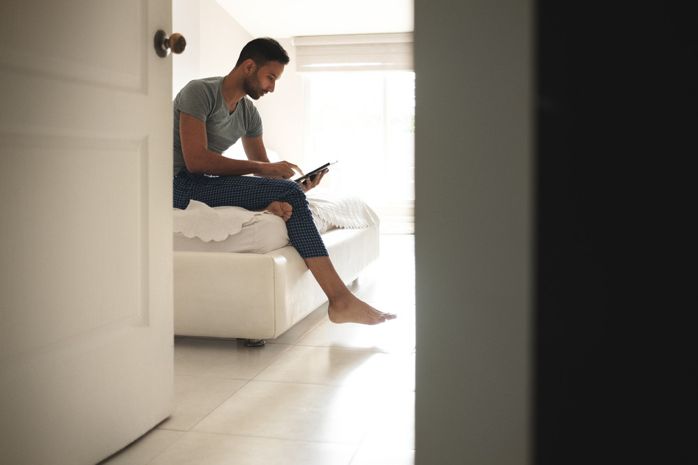 Happy hispanic man sitting on sofa at home with digital tablet. Latino guy addicted to social media, streaming news and videos on computer in bedroom at morning.