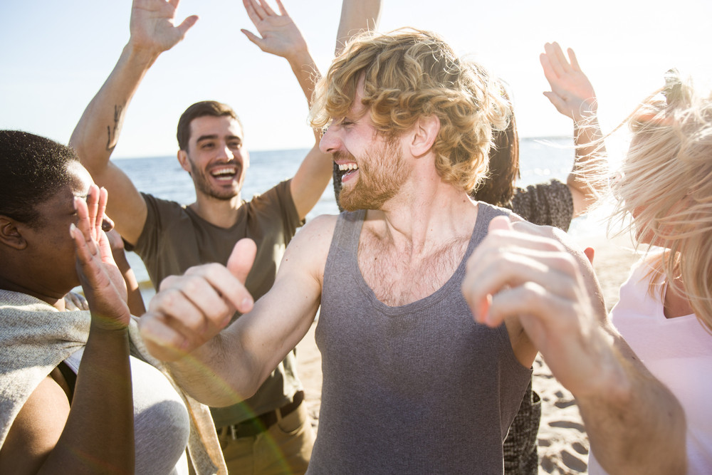 Happy intercultural friends raising hands while dancing on the beach
