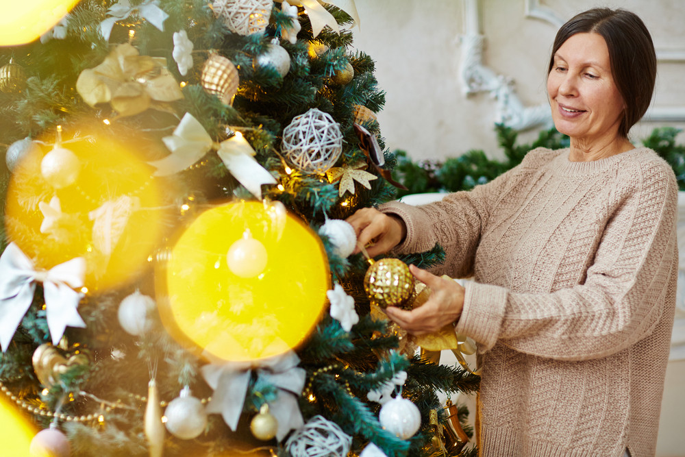 Happy senior female decorating Christmas tree at home