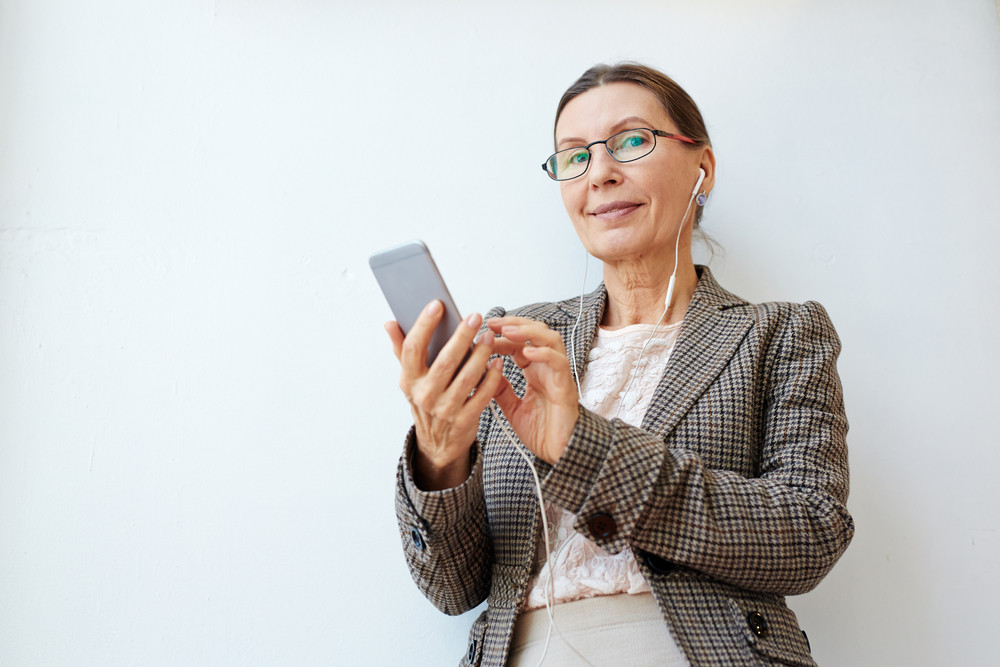 Happy woman with smartphone listening to music