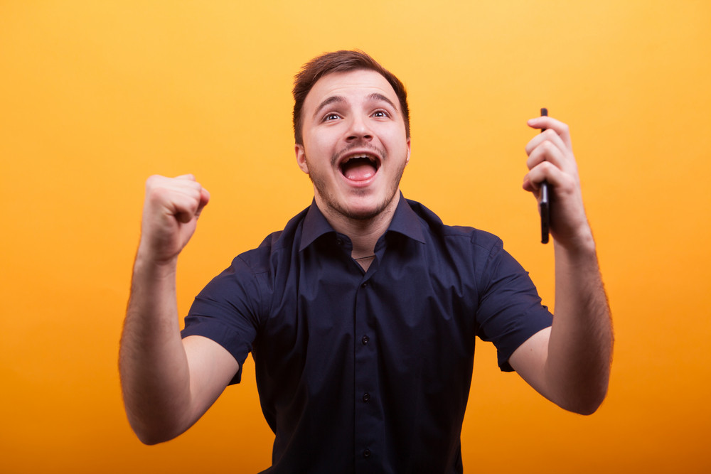 Happy young man in blue shirt hondling mobile phone and celebrating. Shot on yellow background. Showing satisfaction
