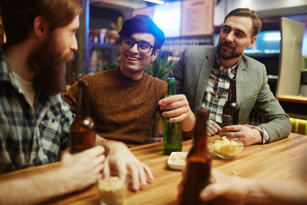 Happy young men with drinks sitting by table in pub and having talk