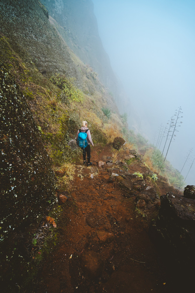 Hiker women with backpack walking down the trekking path. The steep arid slope of the rock. The fog encase the mountain wall
