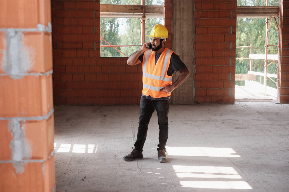 Hispanic man at work in new housing project. Professional latino worker using mobile phone for text message and communications