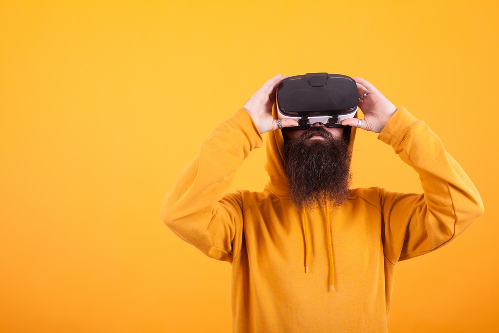 Hispter with long beard wearing yellow hoodie and virtual reality headset over yellow background. Handsome man. Long Beard.