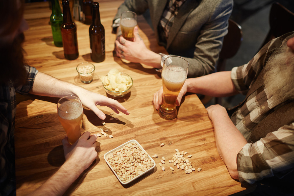 Human hands and glasses of beer on wooden table during friendly conversation in pub on saint Patrick day