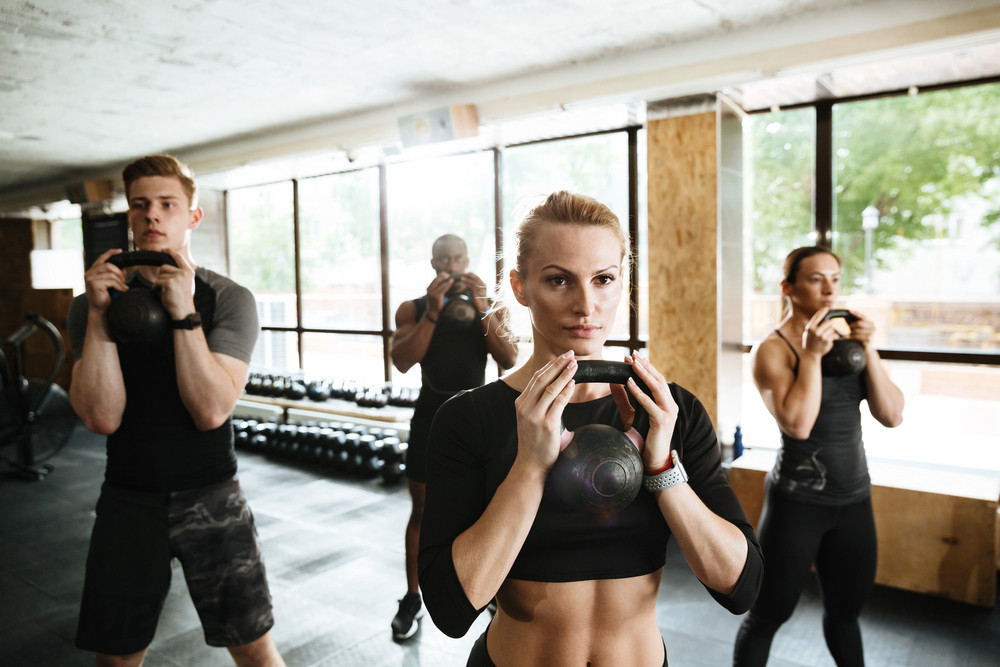 Image of group of multiethnic sports strong people make sport exercise with weight. Looking aside.