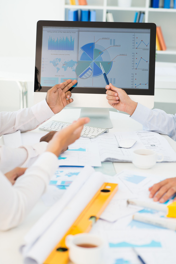 Image of human hands pointing at computer screen in working environment at meeting