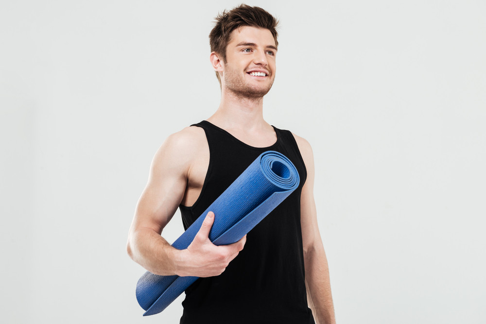 Image of smiling young sportsman standing isolated over white background holding fitness rug. Looking aside.