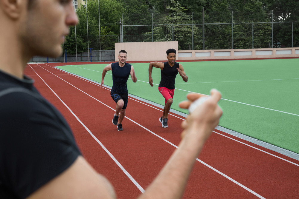 Image of young multiethnic athlete men run on running track outdoors. Historic stop watch time measurement.
