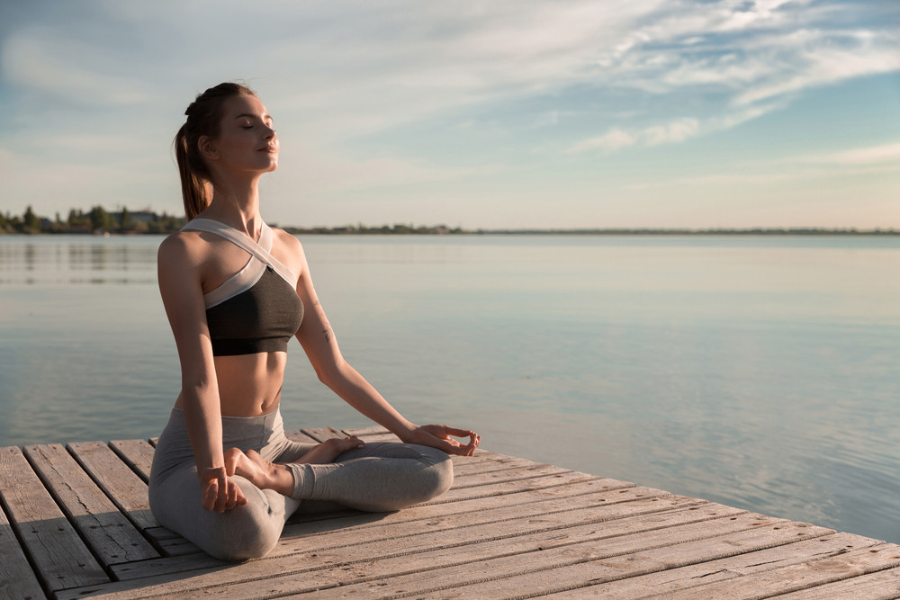 Image of young sports lady at the beach make meditation exercises.
