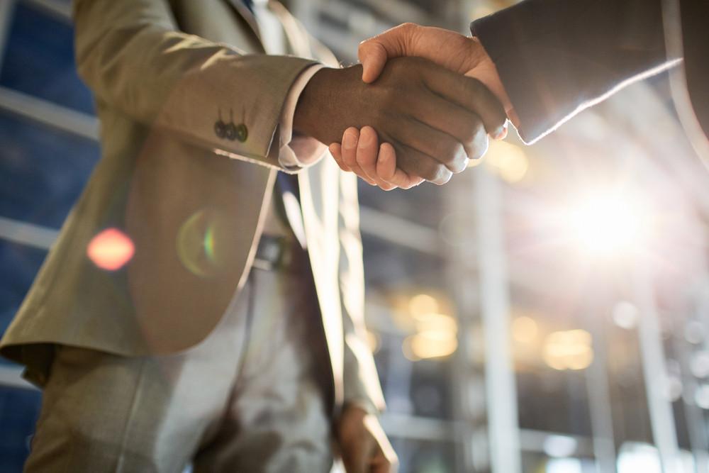 Intercultural traders handshaking after making deal