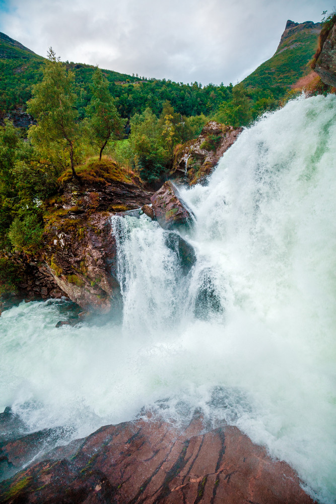 Landscape with beautiful powerful waterfall. Wild nature Norway