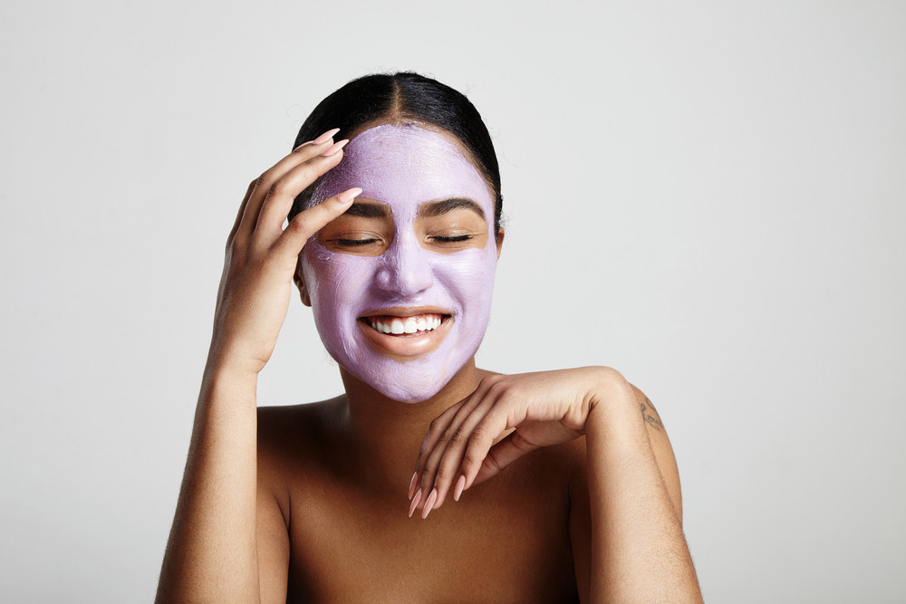laughing woman with a facial mask