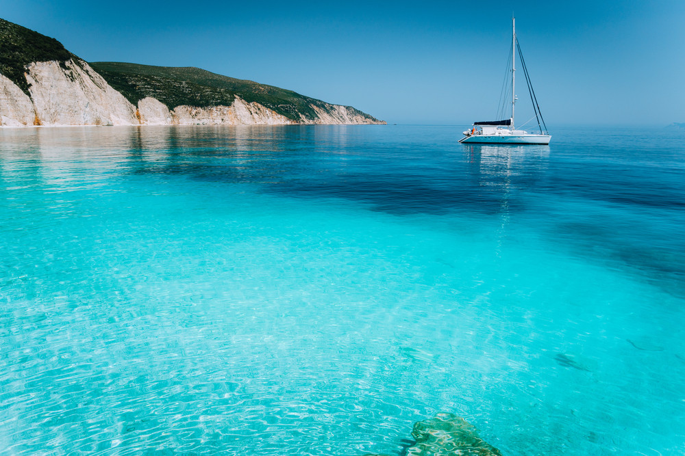 Lonely white sailing catamaran boat drift on calm sea surface. Pure shallow azure blue bay water of a beautiful beach. Scenic landscape of rocky coastline in background