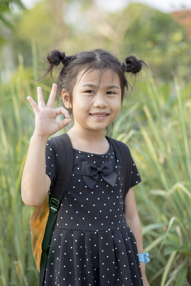 lovely asian children carrying school backpack hand signing o.k. with toothy smiling face
