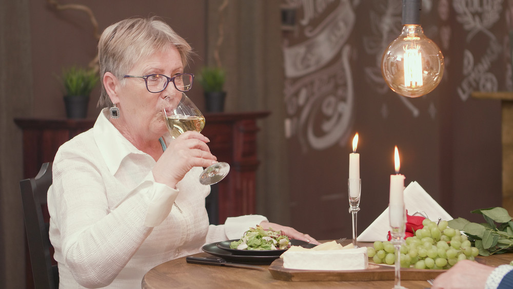 Lovely old lady drinking wine during a romantic date. Romantic old woman. Woman in her sixties.