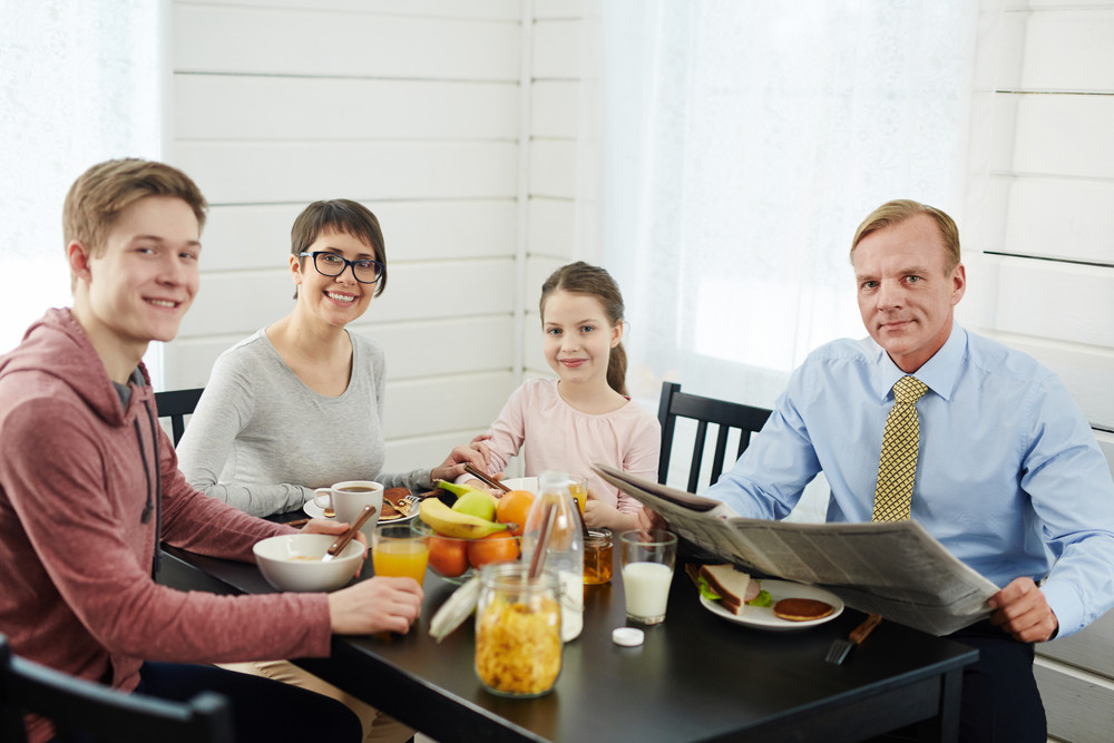 Loving family posing for photography with wide smiles while sitting at breakfast table full of delicious and healthy food, waist-up portrait