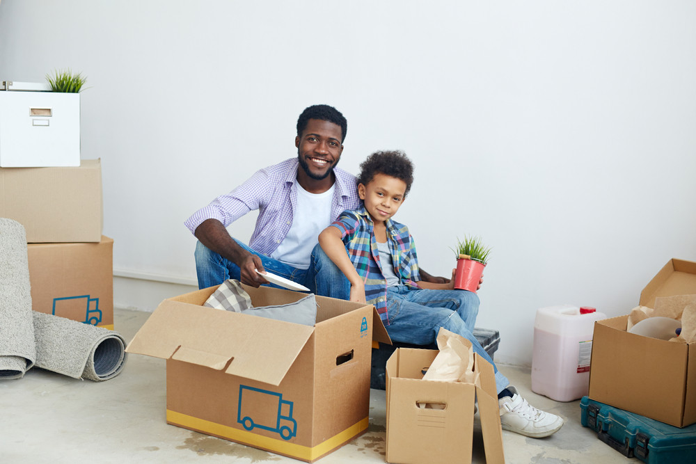 Man and his son unpacking boxes in their new house