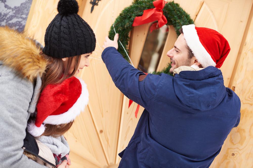 Man hanging the Christmas wreath on the door