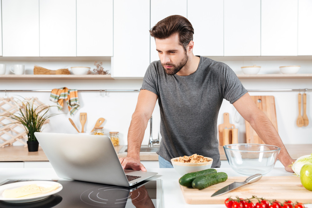Man looking for a recipe on laptop in kitchen at home