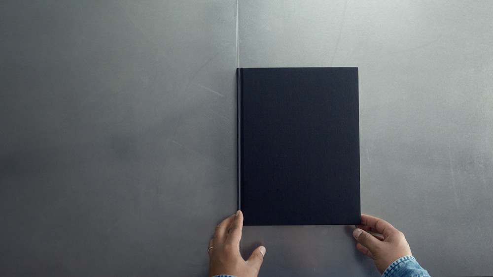 man turning pages of book, magazine with empty white pages