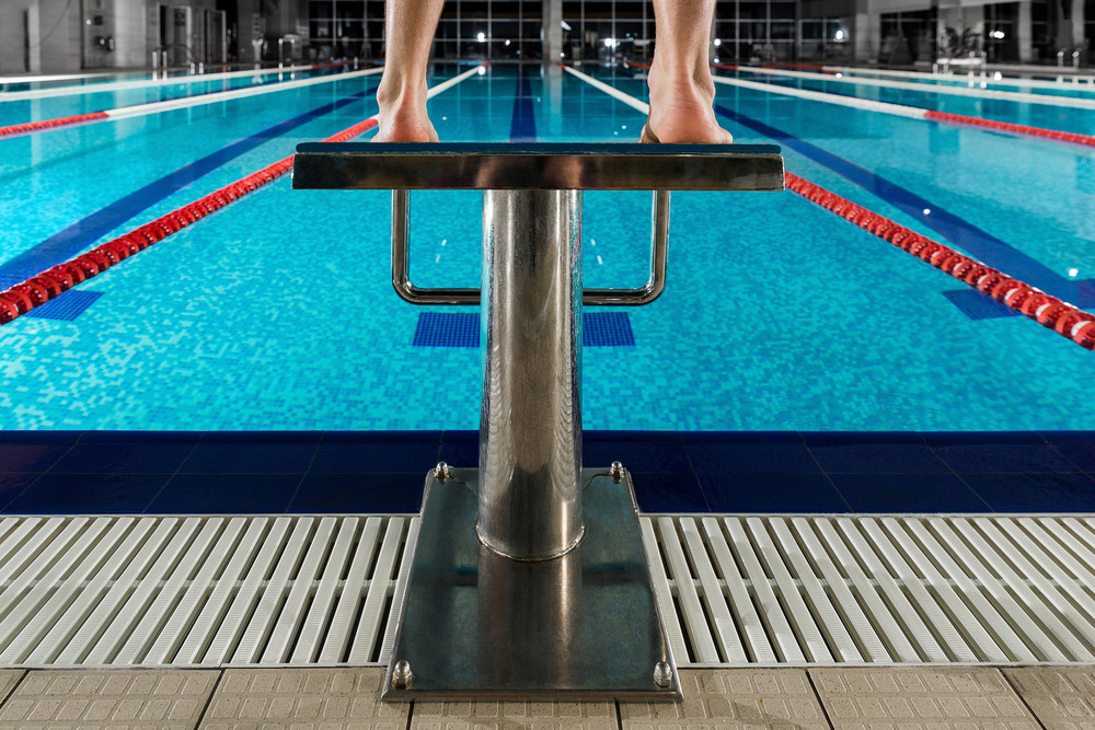 Man\'s feet standing on the starting blocks infront of ...