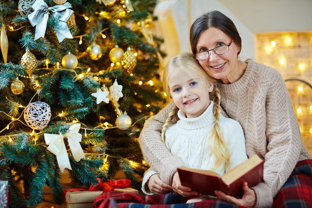 Mature female and little girl with open book looking at camera