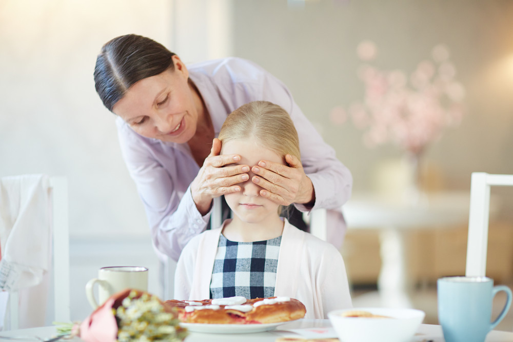 Mature female covering her granddaughter eyes to make surprise