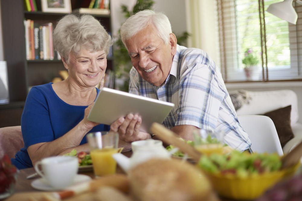 Modern couple of elder people using a touch pad