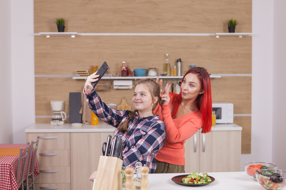 Mother and daughter cooking and taking selfies. Having fun