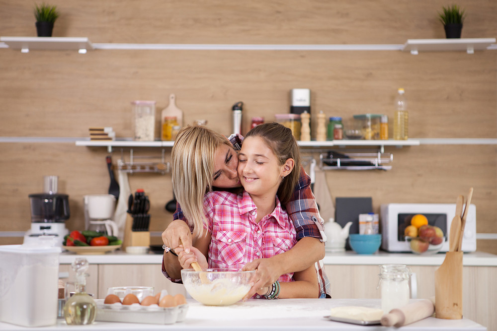 Mother with her daughter cooking in the kitchen. Happy family