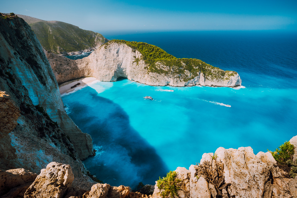 Navagio beach, Zakynthos island, Greece. Tourist boats visiting Shipwreck bay with azure water and paradise white sand beach. Famous landmark location in the world