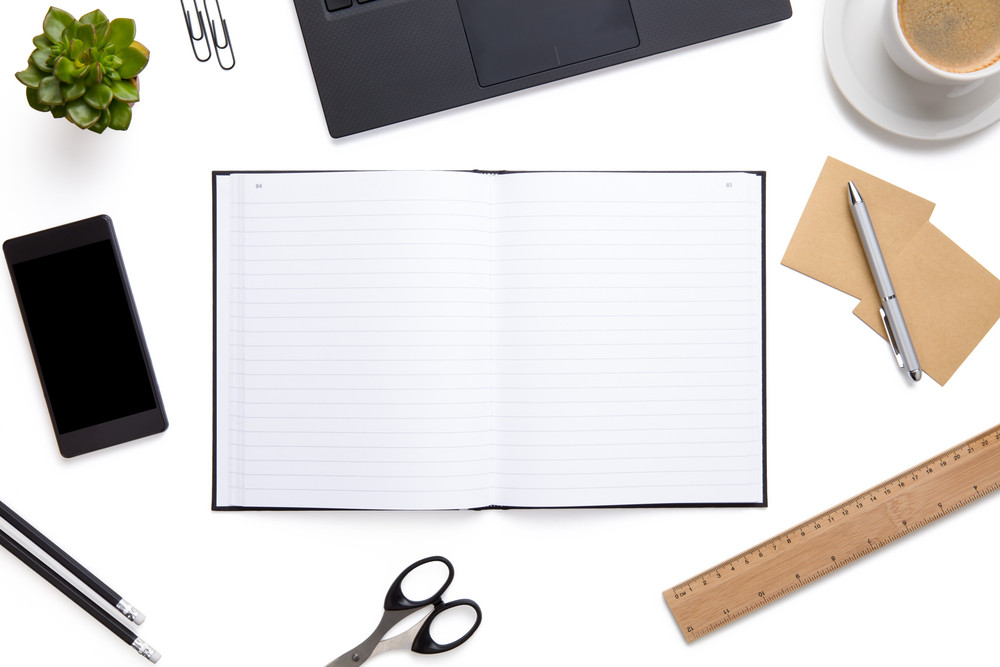 Open Diary Surrounded With Office Supplies On Isolated White Background