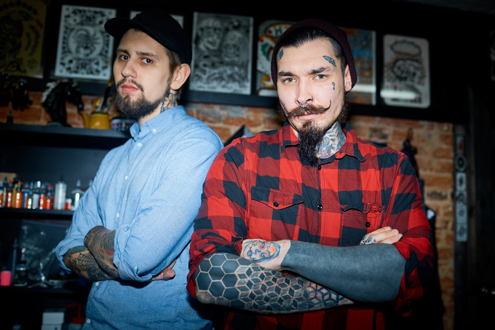 Owner of tattoo salon and his colleague looking at camera