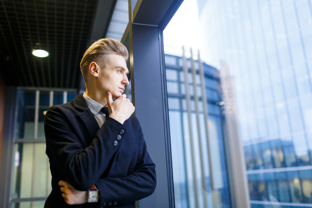 Pensive businessman looking through window of office building