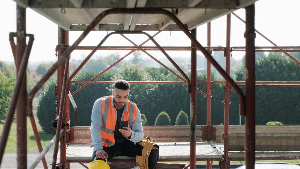 Person working in construction site. White young man at work in new house, smiling and using smartphone for internet and social media during break